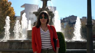 Portrait of happy woman standing close to the fountains in the city, super slow motion