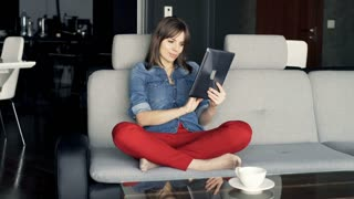 Portrait of happy woman with tablet computer sitting on sofa at home