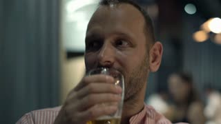Portrait of happy, young man drinking beer in the bar