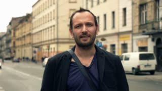 Portrait of happy, young man standing in city, super slow motion 240fps
