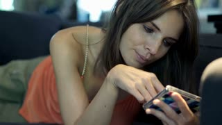 Portrait of happy, young woman with smartphone sitting on sofa