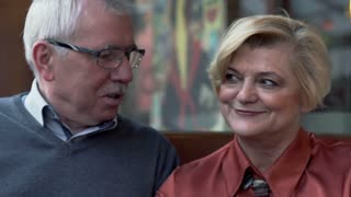 Portrait of middle aged couple talking and smiling to camera in cafe