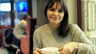 Portrait of pretty, happy young woman drinking coffee in cafe