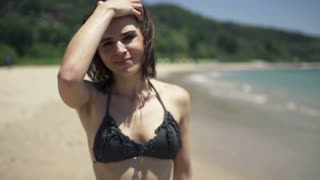 Portrait of sexy woman in bikini standing by the sea, super slow motion, shot at 240fps
