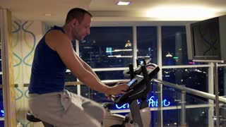 Portrait of young handsome man riding stationary bike in the gym
