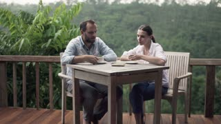 Portrait of young, happy couple drinking coffee on terrace with jungle view