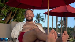 Portrait of young, happy man sitting on sunbed  4K