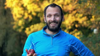 Portrait of young male jogger with apple in autumn forest HD