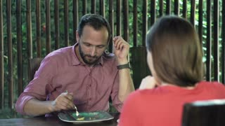 Portrait of young man sitting with his girlfriend during lunch by table at home