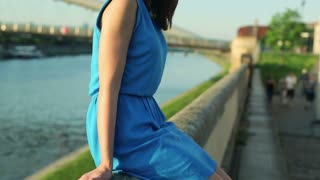 Portrait of young, pretty woman sitting on the bridge by the river