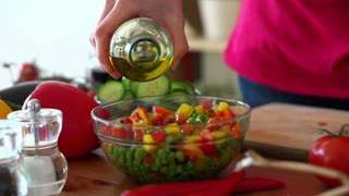 Pouring olive oil on fresh vegetable salad in bowl