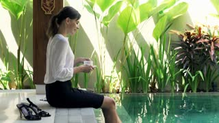 Pretty businesswoman relaxing with coffee sitting on edge by swimming pool