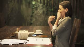 Pretty businesswoman with a cold sitting by table at home at night