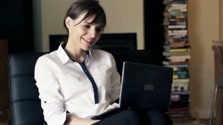 Pretty businesswoman working on laptop sitting by chair at home