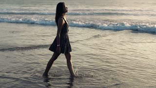 Pretty, happy woman walking on the sea during sunset, slow motion shot at 240fps