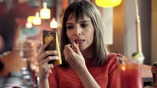 Pretty woman applying lipstick sitting in cafe