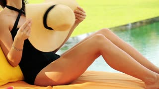 pretty woman cooling herself by hat lying on sunbed