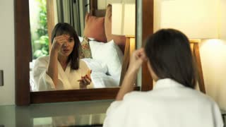 Pretty woman in bathrobe applying makeup, powder on her face in bedroom