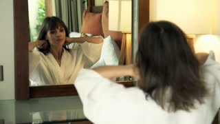 Pretty woman in bathrobe putting necklace on her neck in front of mirror in the bedroom