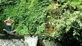 Pretty woman meditating by amazing waterfall