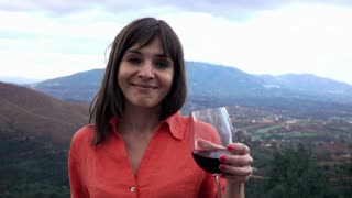 Pretty woman raising toast to camera standing on the terrace with mountains view, 240fps