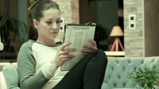 Pretty woman reading magazine sitting on armchair at home