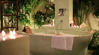pretty woman relaxing in the luxury bathroom at night