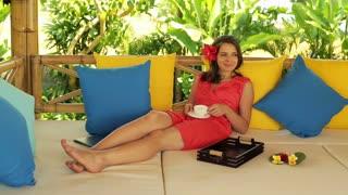 pretty woman relaxing with coffee on gazebo bed in garden