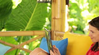 pretty woman relaxing with tablet and coffee on gazebo bed in garden