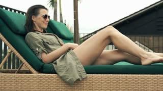 Pretty woman taking off dress and lying in bikini on sunbed