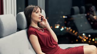 Pretty woman talking on cellphone and drinking wine while sitting on sofa at home during night