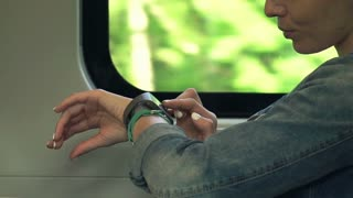 Pretty woman with smartwatch sitting on a train shot at 240fps