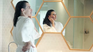 Pretty, young woman in bathrobe talking on cellphone in bathroom
