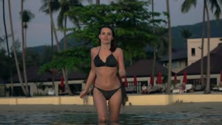 Pretty, young woman in bikini running in the sea, super slow motion