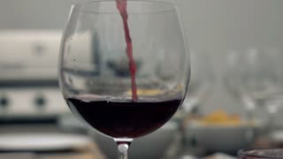Red wine pouring to the glass, super slow motion