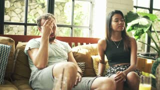 Relationship difficulties, conflicted couple on sofa at home