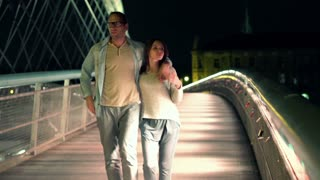 romantic couple walking on bridge in the night