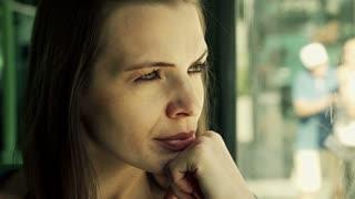 sad, beautiful woman looking through the window of the bus