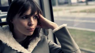 Sad, beautiful woman sitting on the tram ride