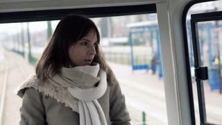 Sad, beautiful woman standing on the tram ride