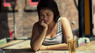 sad, depressed young woman sitting in cafe,