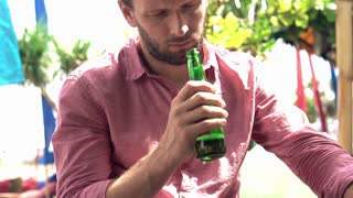 sad, drunk man sitting with beer in beach bar, slow motion, shot at 240fps