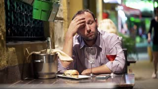 Sad, handsome man drinking wine in bar at night