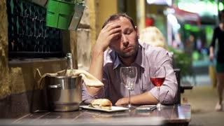 Sad, handsome man drinking wine in bar at night