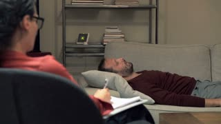 Sad man lying on sofa and talking with therapist