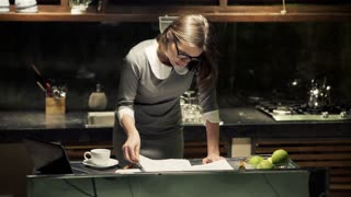 Sad, overwhelmed businesswoman working with documents in the kitchen at night
