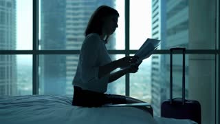 Sad, overwhelmed businesswoman working with documents on bed in the hotel room