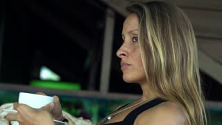 Sad, pensive woman drinking coffee on the terrace, shot at 240fps