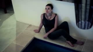 sad pensive woman on the  edge of swimming pole