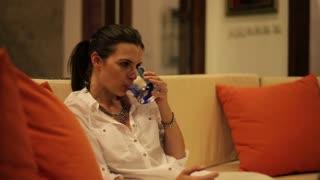 sad pensive woman sitting on the sofa at night